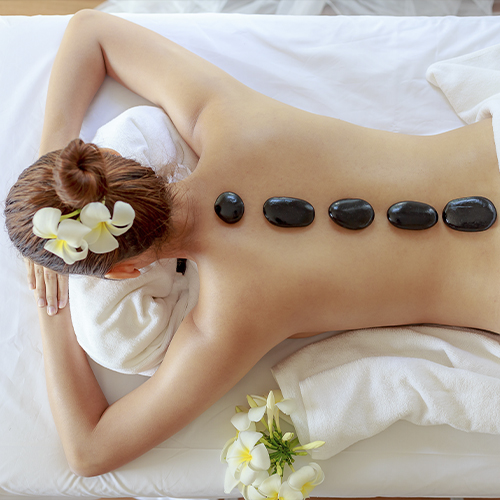 Kvinde med varme sten på ryggen som led i hot stone massage