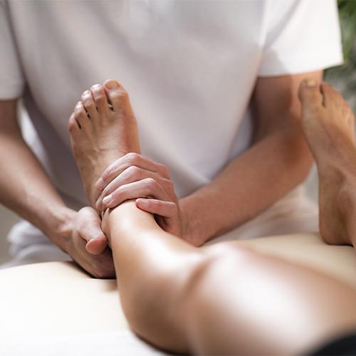 Massør udfører sportsmassage på ben